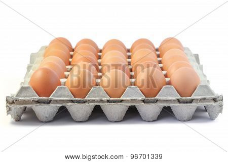 Fresh brown eggs in paper tray on white background