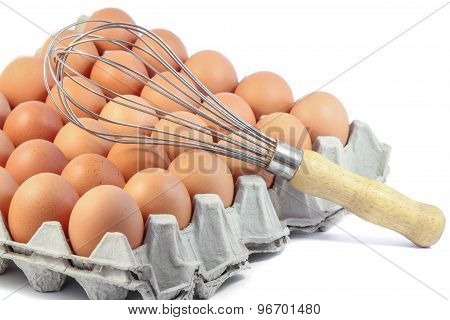Whisk and Fresh Chicken Egg in carton on white background