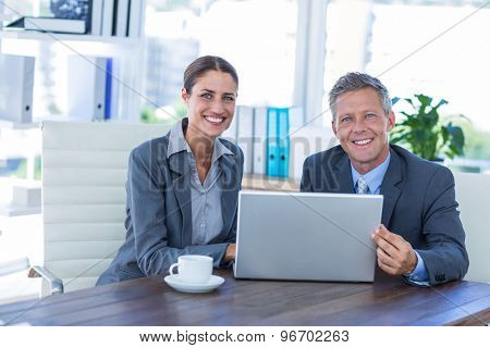 Business people looking at camera and using laptop in office