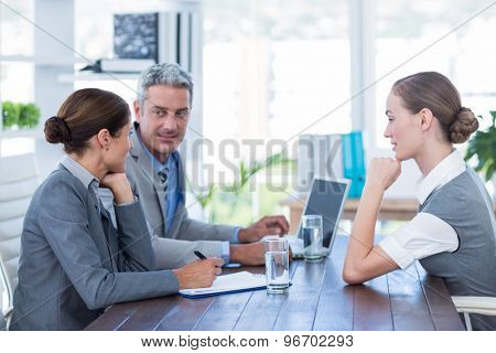 Business people interviewing young businesswoman in office