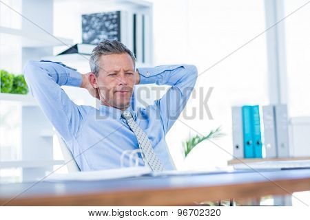 Thoughtful businessman relaxing in swivel chair in office