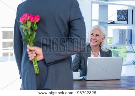 Businessman hiding flowers behind back for colleague in an office
