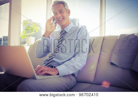 Businessman sitting on a couch having phone call and using laptop in living room