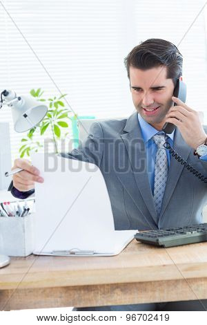 Happy businessman phoning and looking note in the office