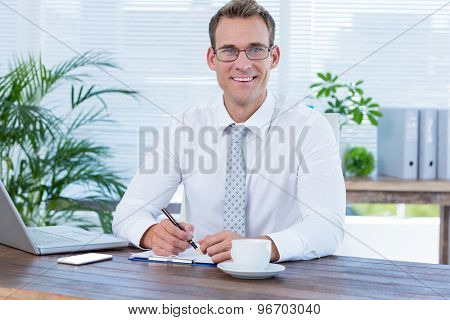 Portrait of a smiling businessman writing on a notebook