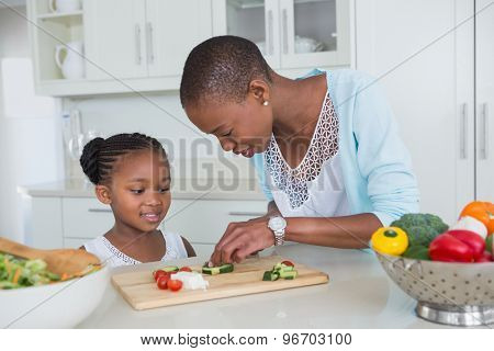 Portrait mother and daughter making a salad together at home in the kitchen
