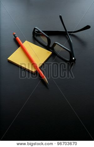 Notepad, pencil and eyeglasses