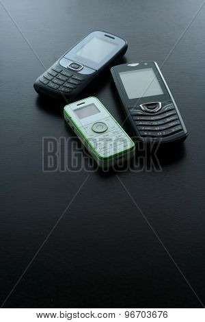 Classic or old cellphones on a wooden table
