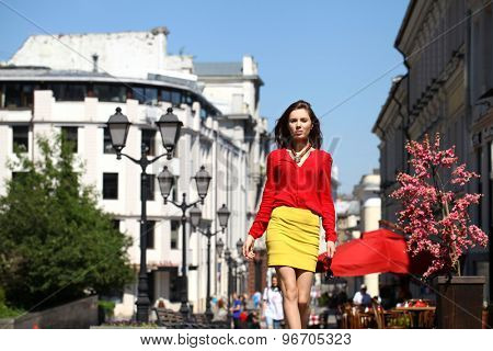 Young beautiful girl in a red blouse and yellow skirt walks down the street