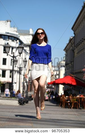 Young beautiful girl in a blue blouse and white skirt walks down the street