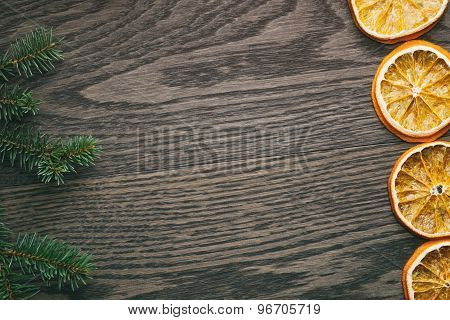 spruce twig with dried orange slices on old table