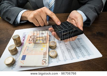 Businessperson Calculating Finance On Desk