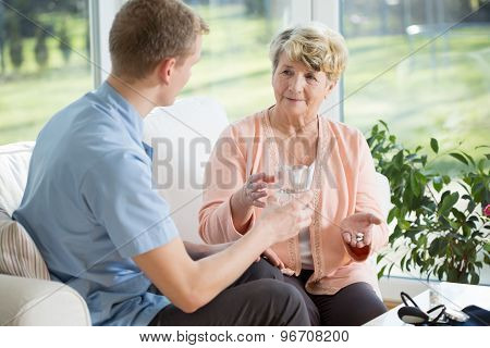 Man Giving Medications To Older Woman