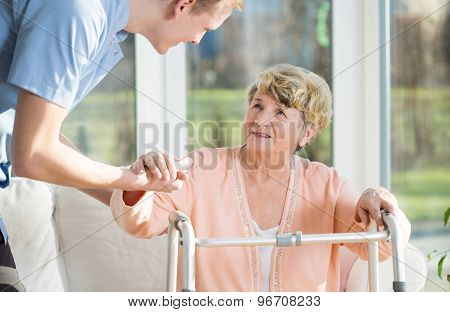Man Helps To Stand Up An Older Woman