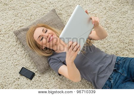 Woman Looking At Digital Tablet While Lying On Carpet
