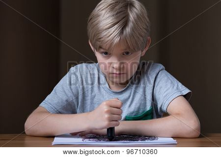 Unhappy Child Holding Black Crayon