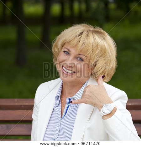 Happy smiling old blonde woman with call me gesture, against green sunner park