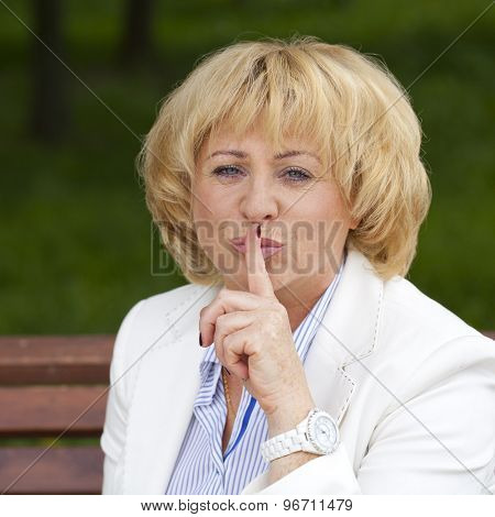 Portrait of old blonde woman with finger on lips, on summer park background concept of student show quiet, silence, secret gesture