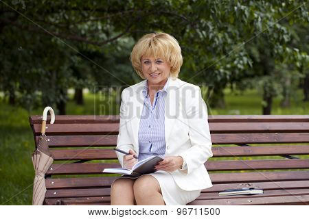 Close up portrait of serene mature woman reading book in the summer park