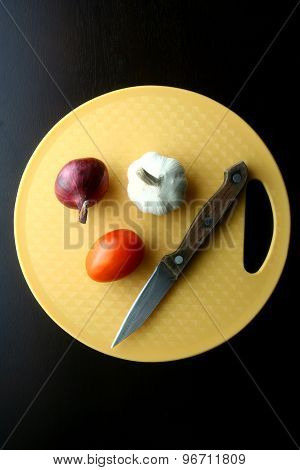Onion, garlic, tomato and knife on chopping board