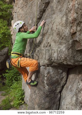 A Young Rock Climber Climbs Difficult Wall.