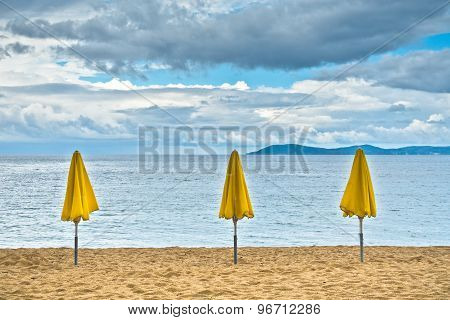 Three yellow sunshades on sandy beach against blue sky, Sithonia