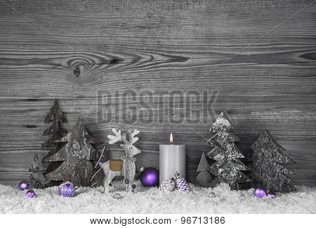 Grey wooden background with handmade reindeer, trees and violet balls.