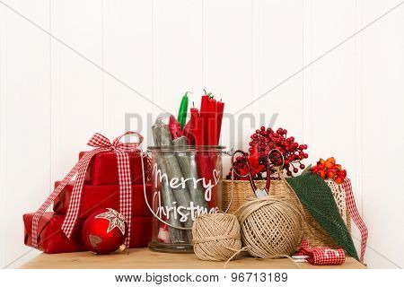 Handmade christmas boxes in red with creative utensils for decoration.
