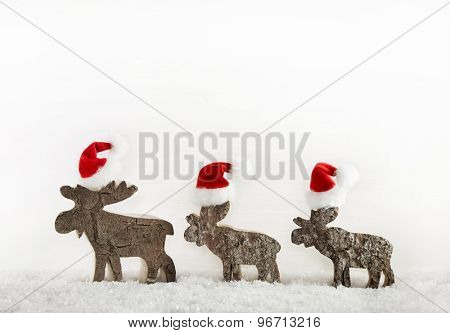 Three wooden handmade reindeer on a background with place for text.