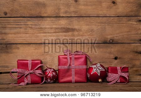 Christmas presents with a red white checked ribbon on old wooden brown background.