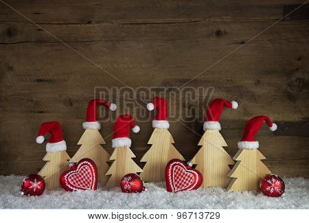 Classical christmas decoration with wood, santa hats on handmade trees and red balls with snow.
