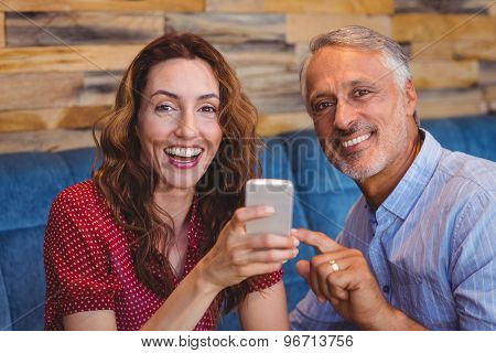 cute couple looking at their phones in the cafe