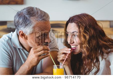 cute couple having glass of orange juice at the cafe
