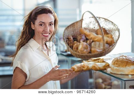 Pretty brunette smiling at camera and holding loaf of bread in the bakery