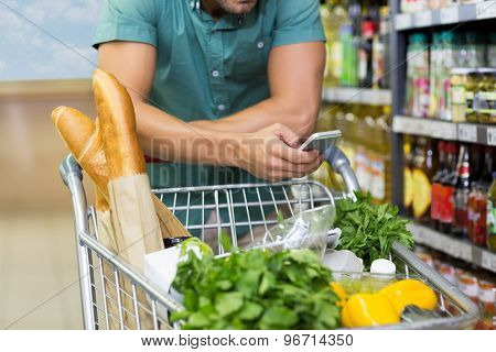 Man buy products and using his smartphone at supermarket