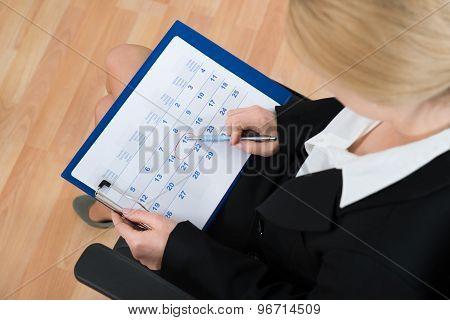 Businesswoman Marking Date On Calendar