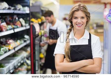 Portrait of smiling pretty blonde woman with arm crossed at supermarket