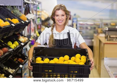 Portrait of a staff woman holding a box with fresh vegetables at supermarket