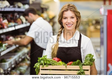 Portrait of smiling staff woman holding a box with fresh vegetables at supermarket