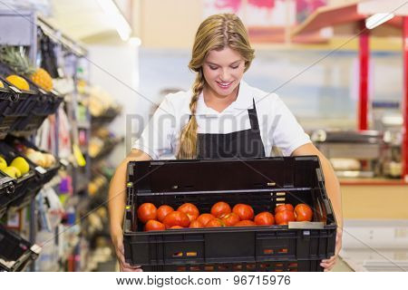Smiling staff woman holding a box with fresh tomatoes at supermarket