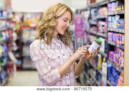 Side view of smiling pretty blonde woman looking at a product in supermarket