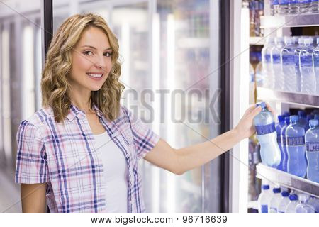 Portrait of a smiling pretty blonde woman taking a water bottle in supermarket
