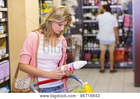 Pretty young woman buying a products in supermarket