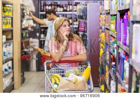 Pretty young woman looking at shelf in supermarket