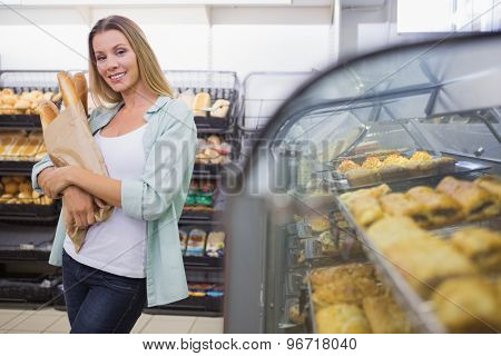 A woman buying bread in the pastries shelf and calling in the supermarket