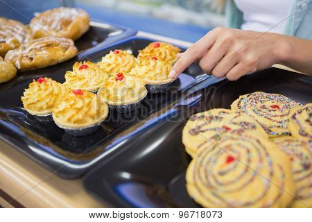 A baker presenting a new plates with pastries in a supermarket