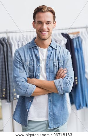 Portrait of a happy smiling man with his arms crossed in the clothing shop