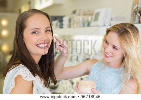 Happy blonde woman applying cosmetic products on her friend in a beauty salon