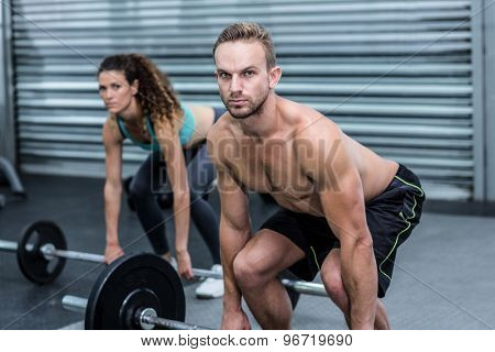 Portrait of a muscular couple lifting weight together