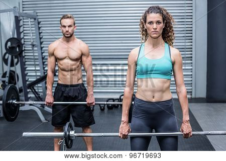 Front view of a muscular couple lifting weight together